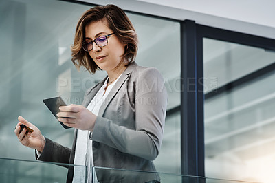 Buy stock photo Shot of a young businesswoman using a smartphone and credit card in a modern office