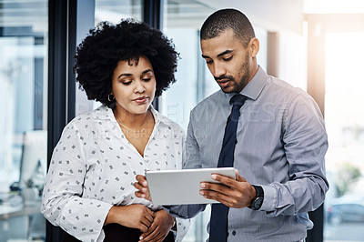 Buy stock photo Shot of a businessman and businesswoman using a digital tablet in a modern office