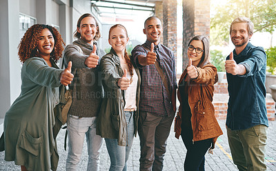 Buy stock photo Portrait of a group of happy young students giving thumbs up together on campus