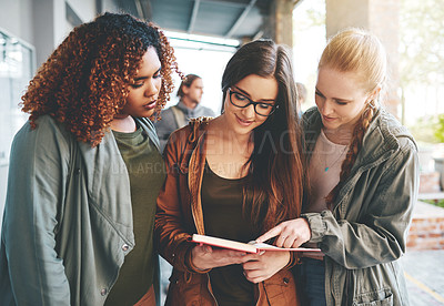 Buy stock photo Shot of a group of young students reading a notebook together on campus