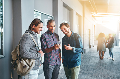 Buy stock photo Shot of a group of young students using a smartphone together outdoors on campus
