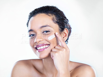 Buy stock photo Studio shot of a beautiful young woman applying moisturiser to her face