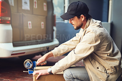Buy stock photo Shot of a courier sealing a ox with tape for delivery