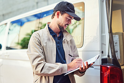 Buy stock photo Shot of a courier checking the deliveries in his van