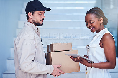 Buy stock photo Shot of a businesswoman using a digital tablet to sign for her delivery from the courier
