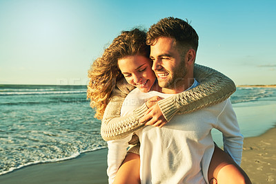 Buy stock photo Cropped shot of a handsome young man piggybacking is girlfriend on the beach