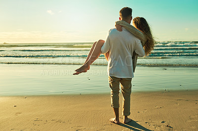 Buy stock photo Rearview shot of a young man carrying his girlfriend on the beach