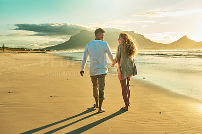 Buy stock photo Rearview shot of an affectionate young couple walking hand in hand on the beach