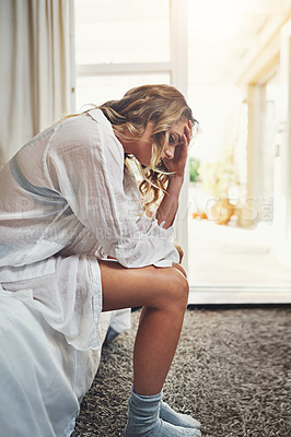 Buy stock photo Shot of a young woman feeling depressed at home