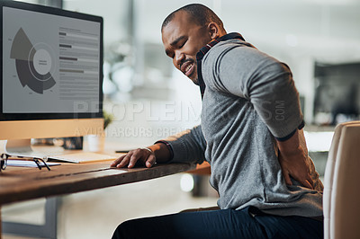 Buy stock photo Cropped shot of a young businessman suffering from backache while working at his desk