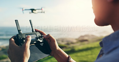 Buy stock photo Shot of an unrecognizable young man flying his drone outdoors