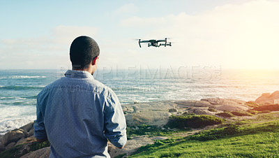 Buy stock photo Rearview shot of a young man flying his drone outdoors
