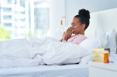 Buy stock photo Shot of a sickly young woman blowing her nose with a tissue in bed at home