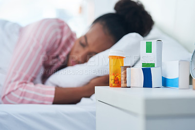 Buy stock photo Shot of an attractive young woman sleeping in bed with her medication on the dresser at home