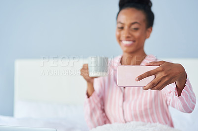 Buy stock photo Shot of an attractive young woman taking a selfie while enjoying her coffee in bed at home