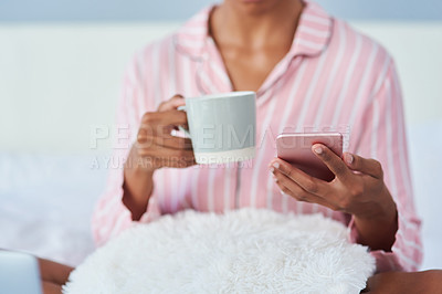 Buy stock photo Shot of an unrecognizable woman drinking coffee and using her cellphone in bed at home