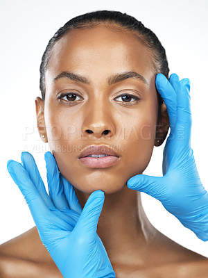 Buy stock photo Studio closeup of an attractive young woman getting her face touched by an unrecognizable person's hands wearing surgical gloves