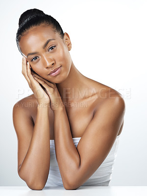 Buy stock photo Studio portrait of an attractive young woman posing and gently touching her face while standing against a white background