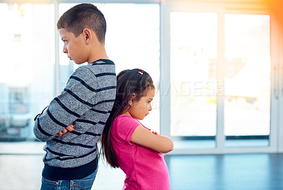 Buy stock photo Shot two naughty young children posing with their arms folded and backs facing each other at home