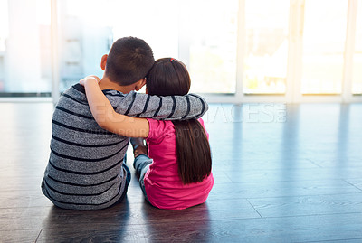 Buy stock photo Rearview shot of two young children sitting on the floor and posing with their arms around each other at home