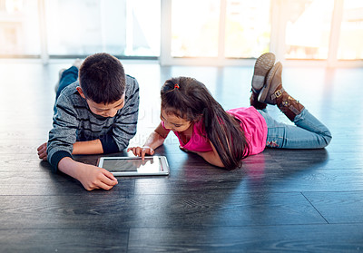 Buy stock photo Shot of two young children using a digital tablet while lying down on the floor at home