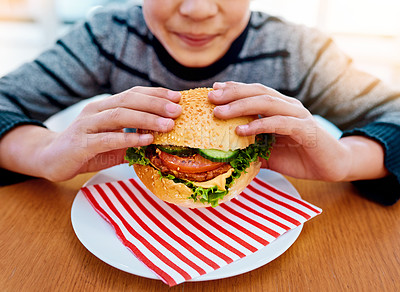 Buy stock photo Shot of an unrecognizable young boy eating a delicious burger while sitting at his table at home