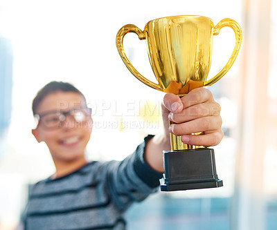 Buy stock photo Shot of an intelligent young boy proudly holding his academics trophy at home
