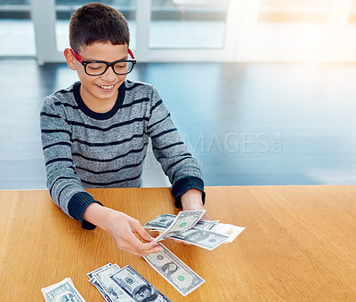 Buy stock photo Shot of a focused young boy counting his money on the dinner table at home
