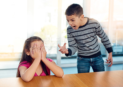 Buy stock photo Shot of a little girl covering her face while her brother angrily screams at her at home