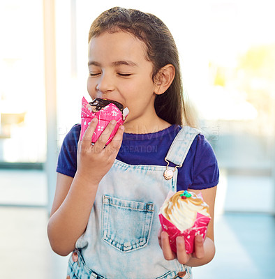 Buy stock photo Shot of an adorable little girl eating a delicious cupcake at home