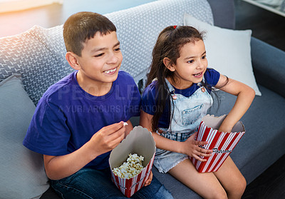 Buy stock photo Shot of two young children sitting on a sofa and eating popcorn while watching movies at home