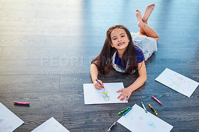 Buy stock photo Full length shot of a young girl lying down on the floor and coloring in pictures in her coloring book at home