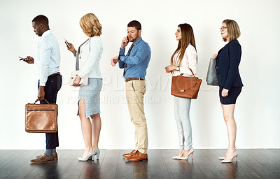 Buy stock photo Studio shot of a group o focused people standing in a row behind each other against a white background