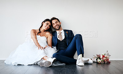 Buy stock photo Studio shot of a newly married young couple sitting together on the floor against a gray background