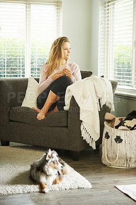Buy stock photo Shot of a young woman using a smartphone while relaxing while relaxing at home with her dog