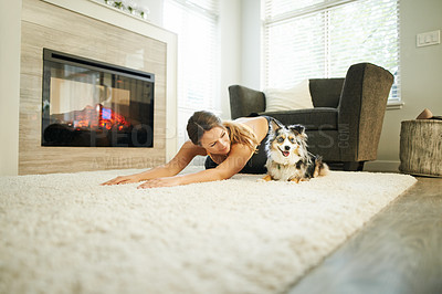 Buy stock photo Shot of a young woman exercising at home with her dog keeping her company
