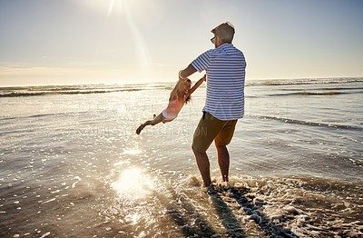 Buy stock photo Shot of a little girl having fun with her father at the beach