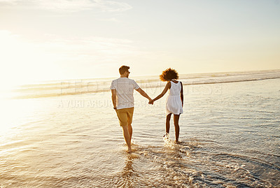 Buy stock photo Shot of a young couple bonding at the beach