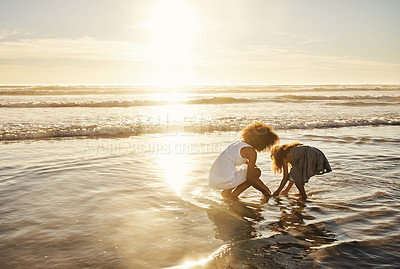 Buy stock photo Rearview shot  of a mother and her little daughter picking up seashells at the beach