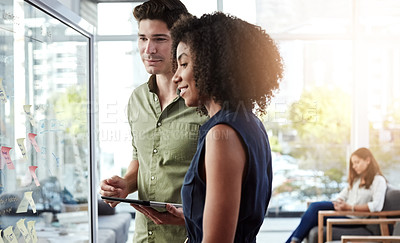 Buy stock photo Shot of two businesspeople brainstorming on a glass screen in an office