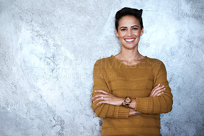 Buy stock photo Portrait of a confident young businesswoman standing with her arms folded against a grey wall