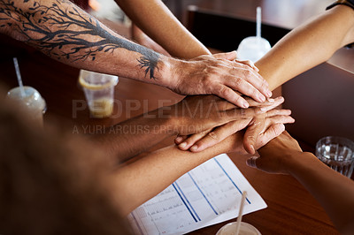 Buy stock photo High angle shot of a group of unrecognizable designers with their hands in a huddle during a meeting in their creative office