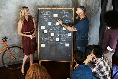 Buy stock photo Full length shot of a handsome mature businessman and his female associate giving a presentation to his colleagues in the office
