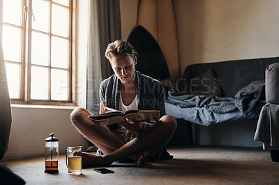 Buy stock photo Shot of a young man reading a book while sitting on the floor at home