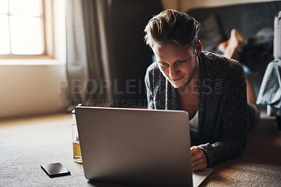 Buy stock photo Shot of a handsome young man using his laptop while lying down on the floor at home