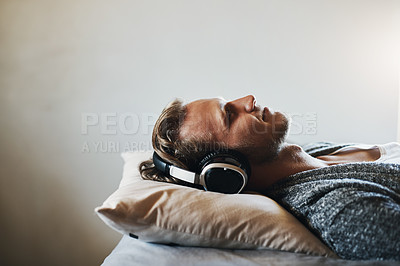 Buy stock photo Shot of a handsome young man listening to music on his headphones while relaxing in bed at home