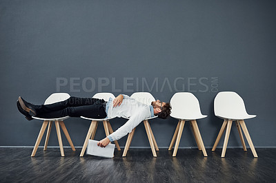 Buy stock photo Full length shot of a handsome young man lying down on a row of chairs while waiting in line for a job interview