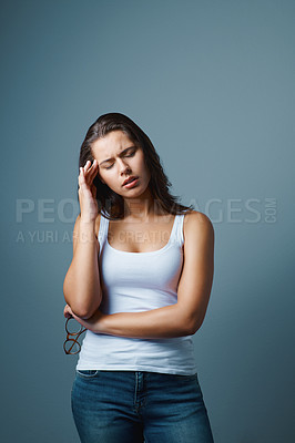 Buy stock photo Studio shot of an attractive young woman suffering from a headache