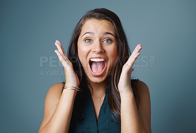 Buy stock photo Studio shot of an attractive young woman looking surprised against a blue background
