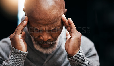 Buy stock photo Shot of a handsome senior man rubbing his temples in pain